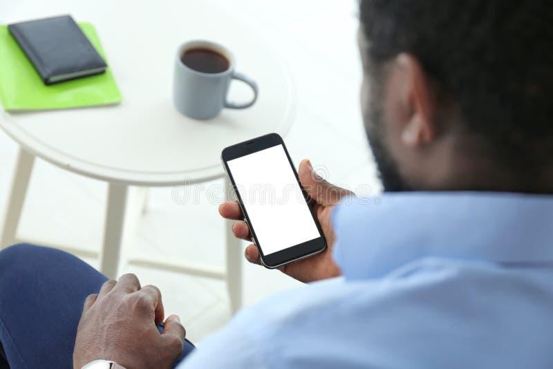Telefono cellulare afroamericano della tenuta dell'uomo immagini stock libere da diritti