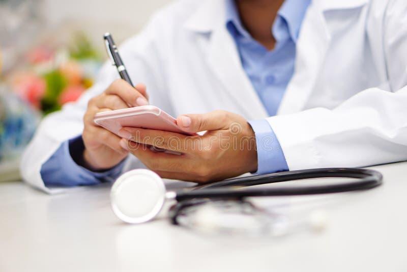 Telefono cellulare attivo asiatico della tenuta di medico da comunicare circa lavoro all'ospedale fotografia stock