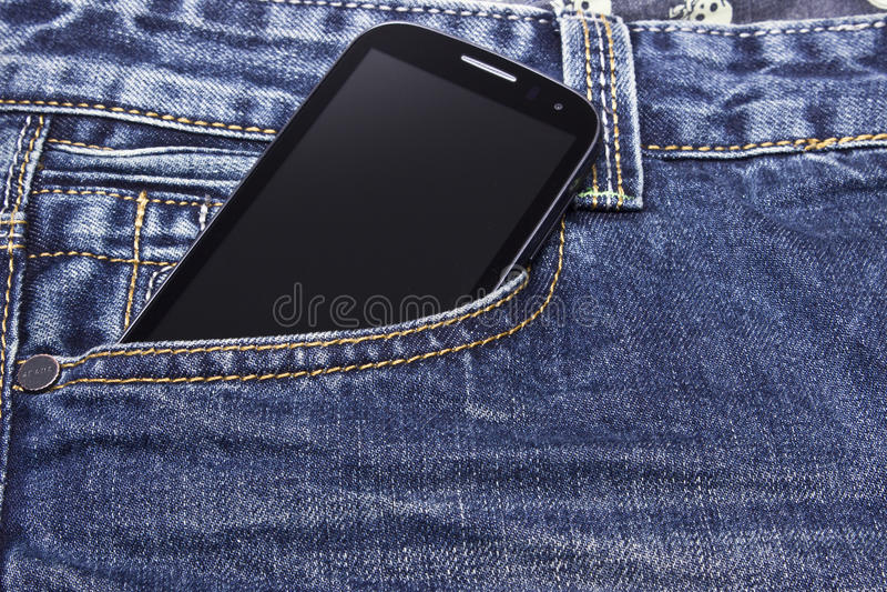 Telefono cellulare in blue jeans immagine stock