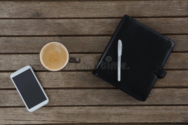 Telefono cellulare, caffè, penna ed organizzatore sulla plancia di legno fotografie stock