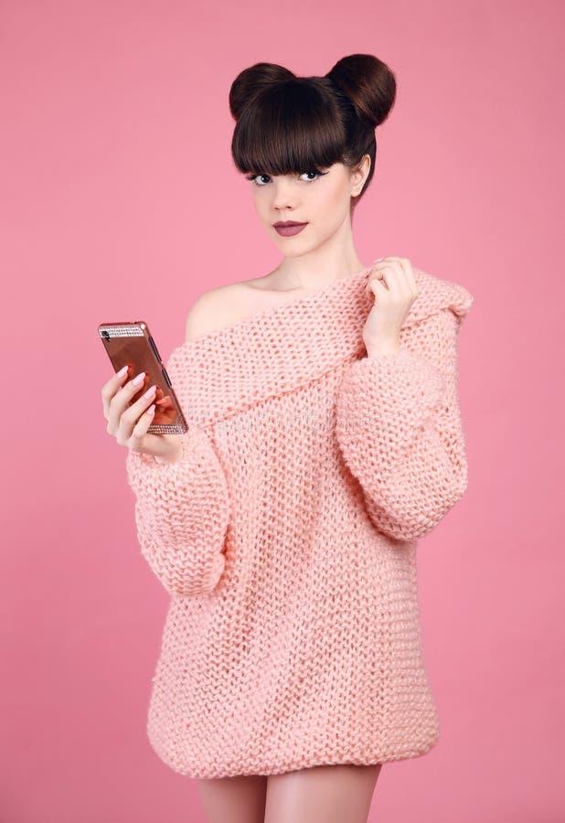 Telefono cellulare castana della tenuta Styl teenager di sguardo dello studio di modo immagini stock libere da diritti