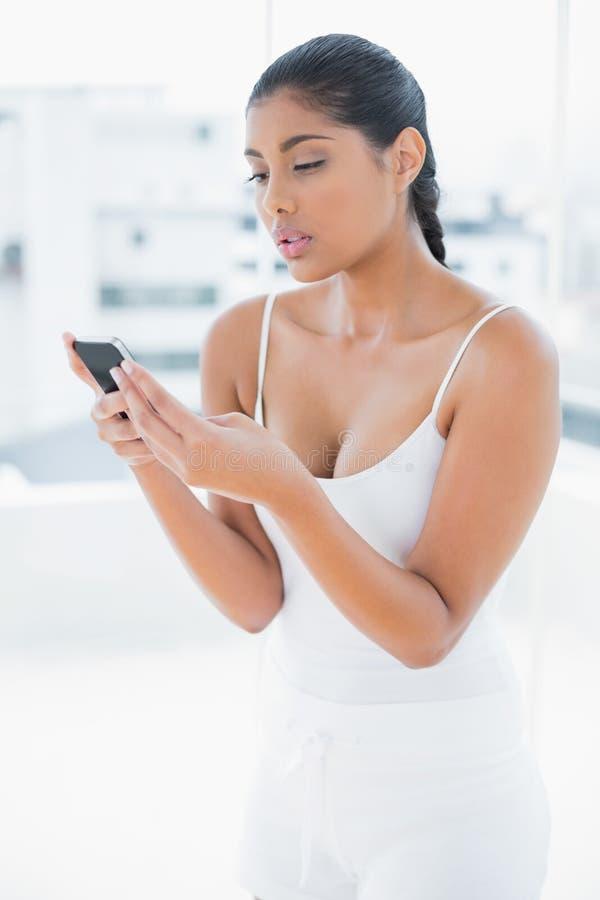 Telefono cellulare castana tonificato aggrottante le sopracciglia della tenuta fotografia stock libera da diritti
