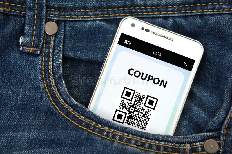 Telefono cellulare con il buono di sconto in tasca immagini stock