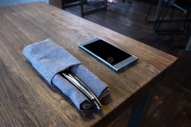 Telefono cellulare con l'insieme della coltelleria sulla tavola di legno in ristorante Concetto di dipendenza di Smartphone Alime fotografia stock