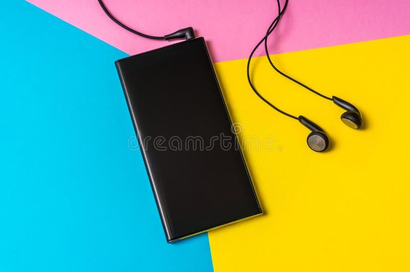 Telefono cellulare con le cuffie isolate su fondo variopinto immagine stock