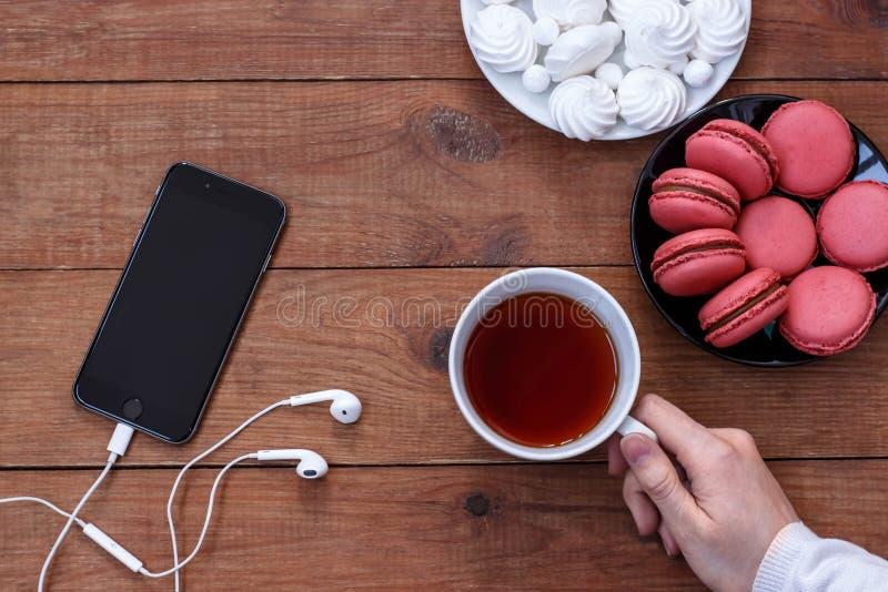 Telefono cellulare con le cuffie, la meringa, i maccheroni e una tazza di tè su fondo di legno immagine stock