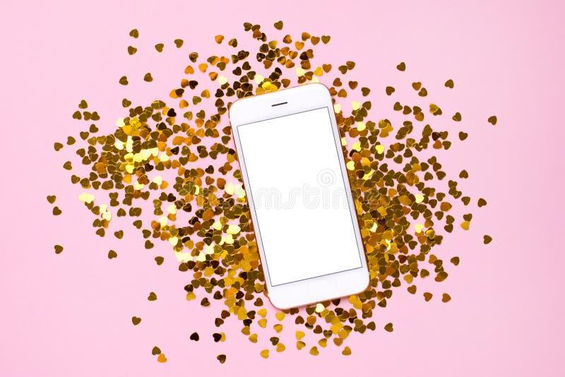Telefono cellulare con lo schermo vuoto bianco sul fondo rosa della carta di colore con i coriandoli dorati del cuore immagini stock libere da diritti