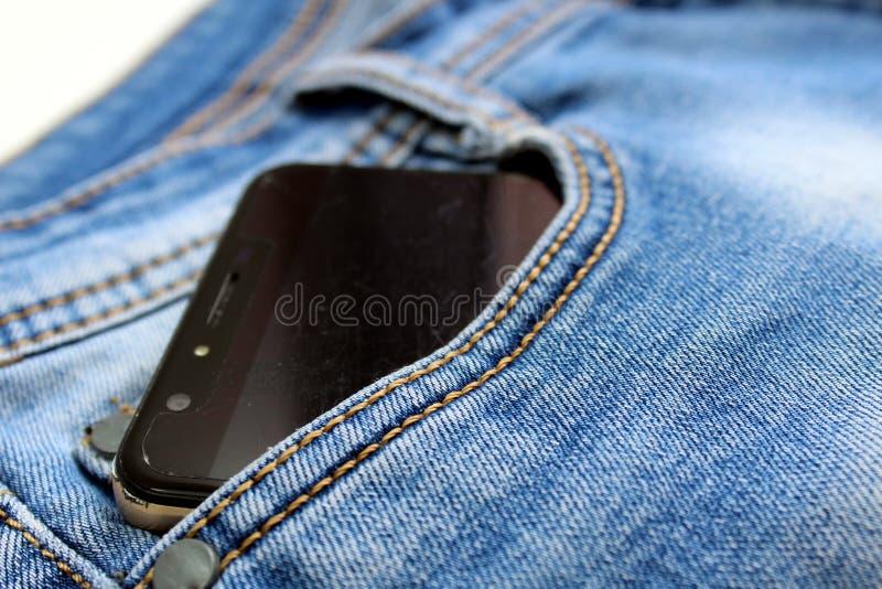 Telefono cellulare con uno schermo nero nella tasca dei pantaloni del denim immagine stock libera da diritti