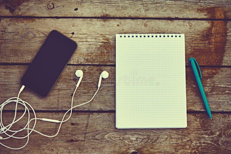 Telefono cellulare, cuffie, taccuino e penna sulla vecchia tavola di legno immagine stock libera da diritti