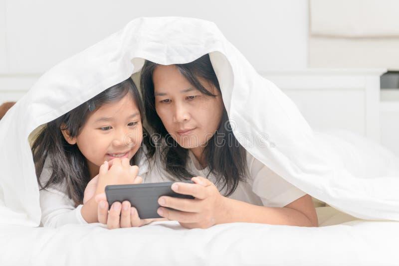 Telefono cellulare del gioco della figlia e della madre sul letto fotografia stock