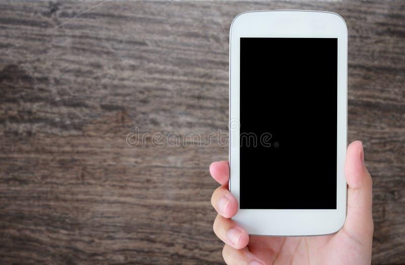Telefono cellulare della tenuta della mano sopra il vecchio pavimento di legno fotografia stock