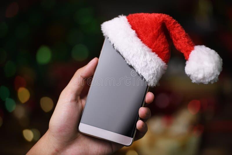 """Telefono cellulare della tenuta della mano con il cappello di Santa Claus """"sulla cima sul Natale fotografia stock"""