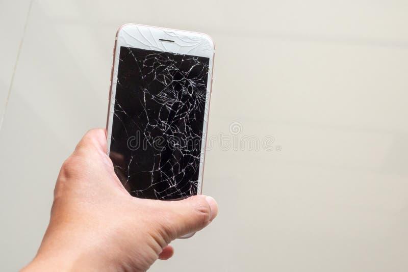 Telefono cellulare della tenuta della mano con lo schermo di vetro rotto fotografie stock