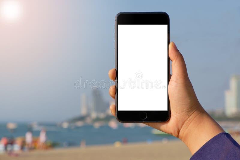 Telefono cellulare della tenuta della mano della donna del primo piano sul bello fondo fresco del cielo blu e della sabbia di mar fotografie stock libere da diritti