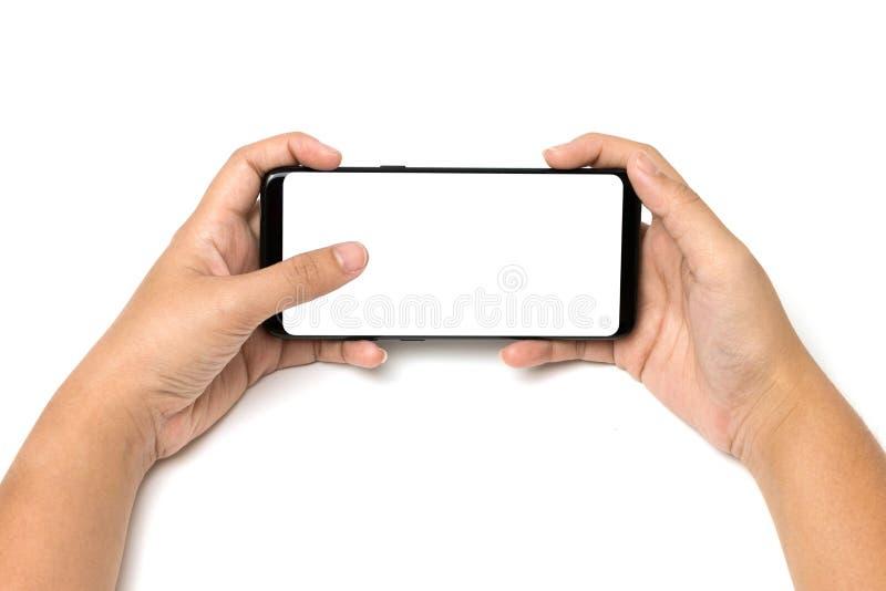Telefono cellulare della tenuta della mano e tocco del dito sullo schermo bianco in bianco immagini stock