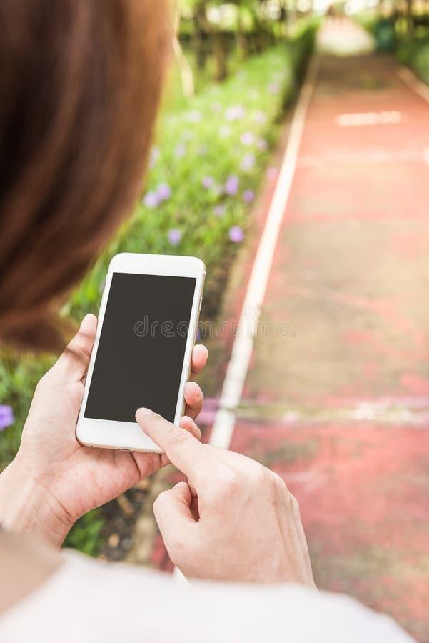 telefono cellulare della tenuta della mano nel giardino immagine stock libera da diritti