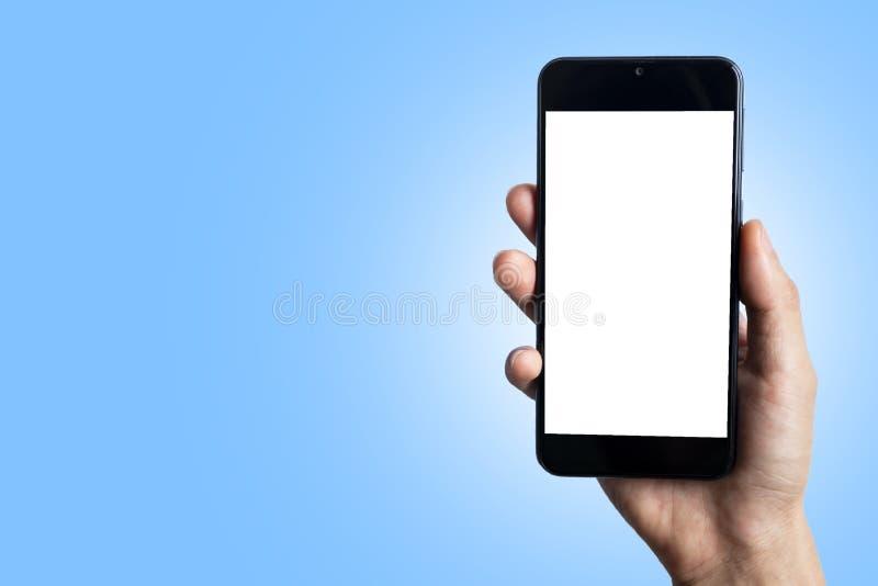 Telefono cellulare della tenuta della mano nello splendere fondo blu immagine stock libera da diritti