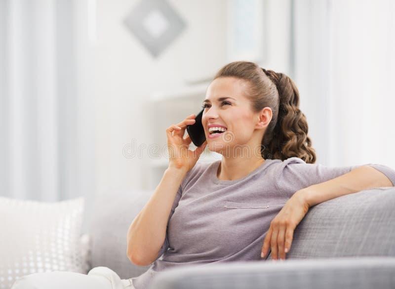 Telefono cellulare di conversazione della giovane casalinga felice in salone immagine stock