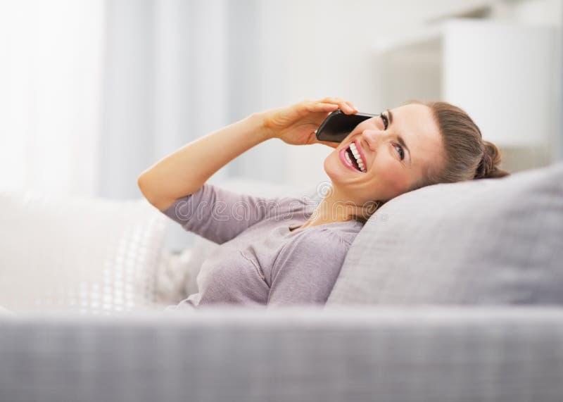 Telefono cellulare di conversazione della giovane donna felice mentre sedendosi sullo strato immagine stock