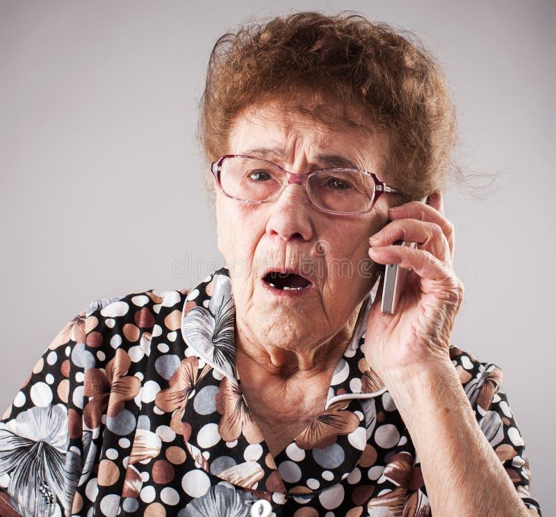 Telefono cellulare di conversazione femminile degli anziani immagine stock