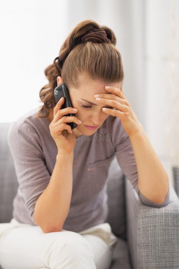 Telefono cellulare di conversazione frustrato della giovane donna fotografia stock