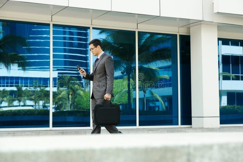 Telefono cellulare di Reading Email On dell'uomo d'affari che cammina all'ufficio immagine stock libera da diritti