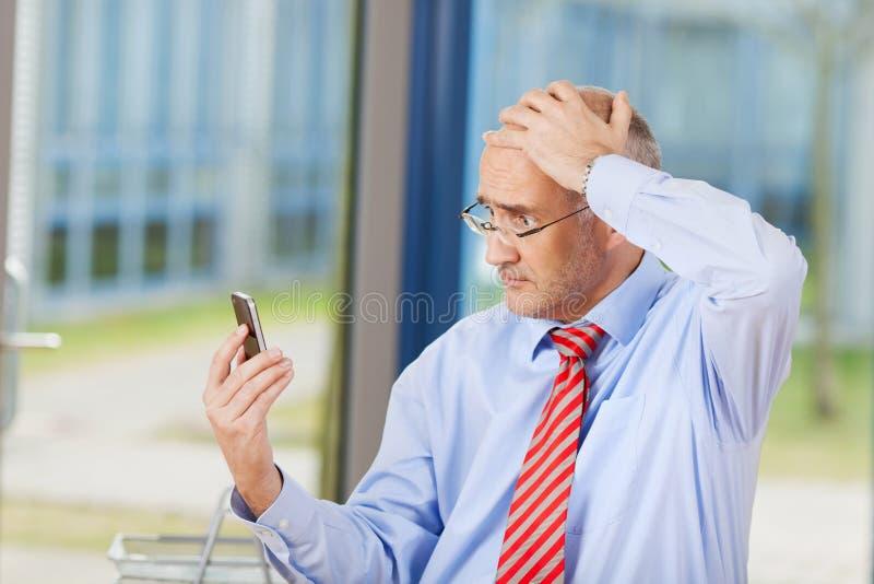 Telefono cellulare di Reading Message On dell'uomo d'affari immagini stock