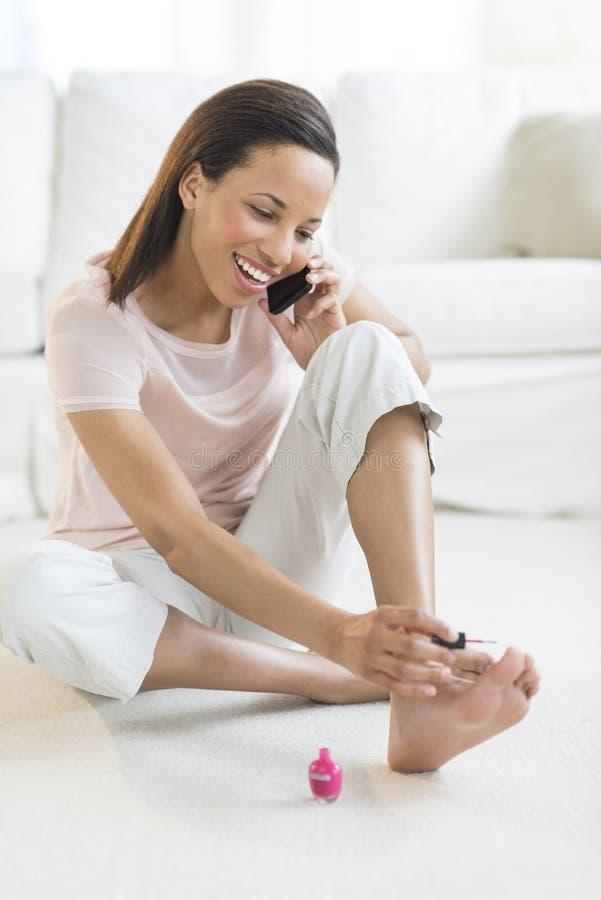 Telefono cellulare di risposta della donna mentre dipingendo le unghie del piede a casa fotografie stock libere da diritti