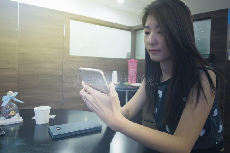 Telefono cellulare di uso della mano della donna per collegamento a Internet o acquisto fotografia stock
