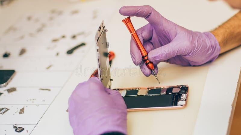 Telefono cellulare difettoso di riparazione del tecnico in smartphone elettronico t fotografia stock