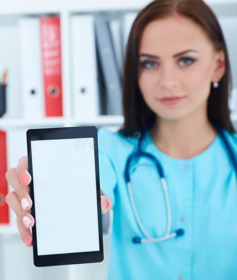Telefono cellulare e rappresentazione femminili della tenuta di medico della medicina alla macchina fotografica Therapeutist face fotografia stock libera da diritti