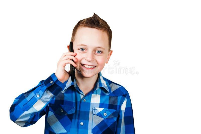 Telefono cellulare e sorrisi della tenuta del ragazzo, isolati su fondo bianco fotografia stock libera da diritti