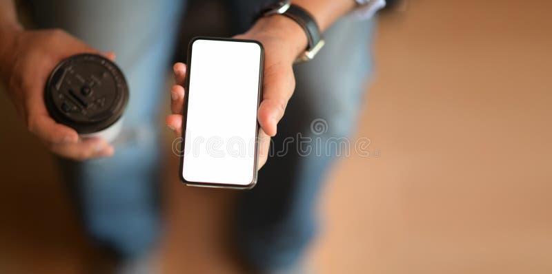 Telefono cellulare e tazza da caffè della tenuta dell'uomo immagine stock libera da diritti