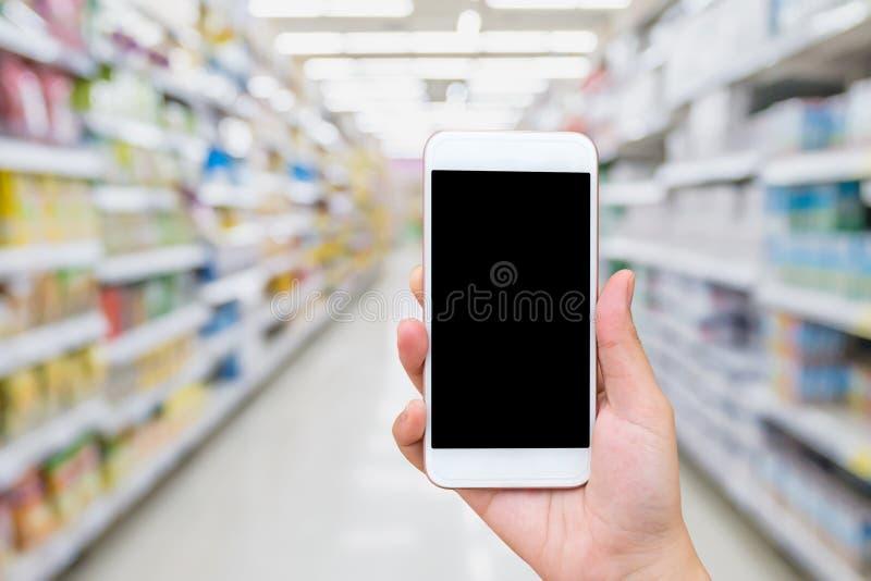 Telefono cellulare femminile della tenuta della mano con il fondo del supermercato fotografie stock