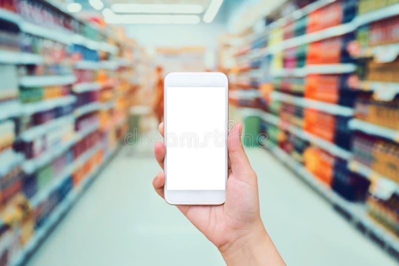 Telefono cellulare femminile della tenuta della mano con il fondo del supermercato immagini stock libere da diritti