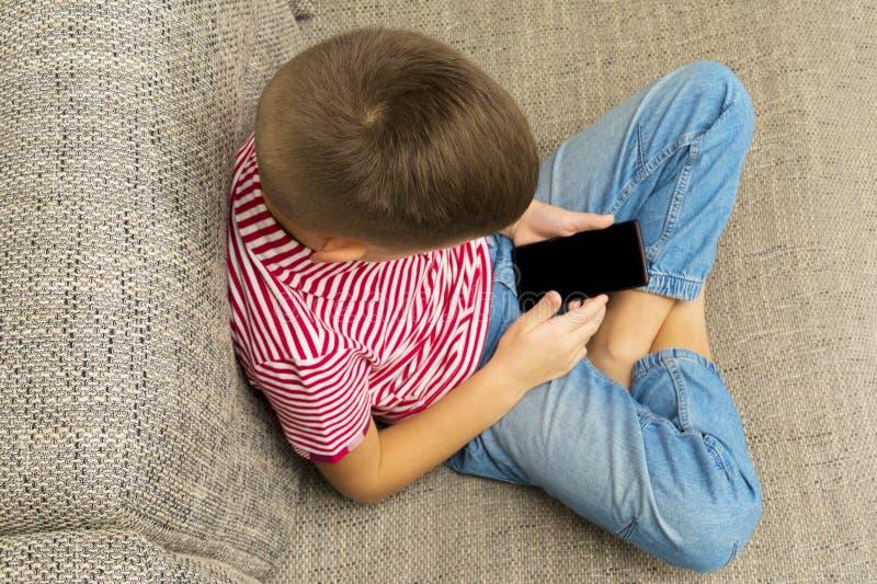 Telefono cellulare in mani del ragazzo con il touchscree in bianco nero immagini stock libere da diritti