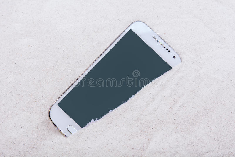Telefono cellulare sepolto nella sabbia immagini stock libere da diritti
