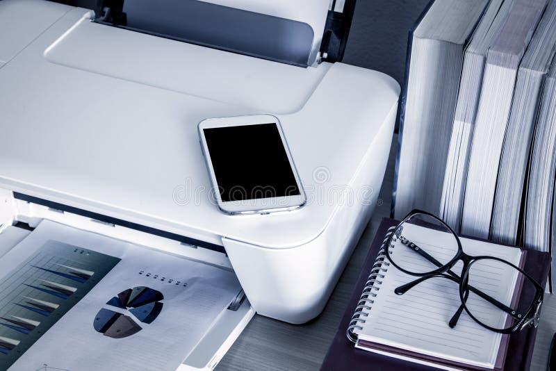 Telefono, cellulare, Smart Phone sulla stampante con i libri immagini stock libere da diritti