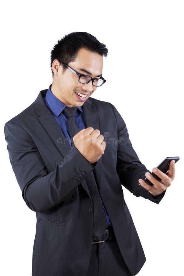 Telefono cellulare soddisfatto della tenuta dell'uomo d'affari fotografie stock