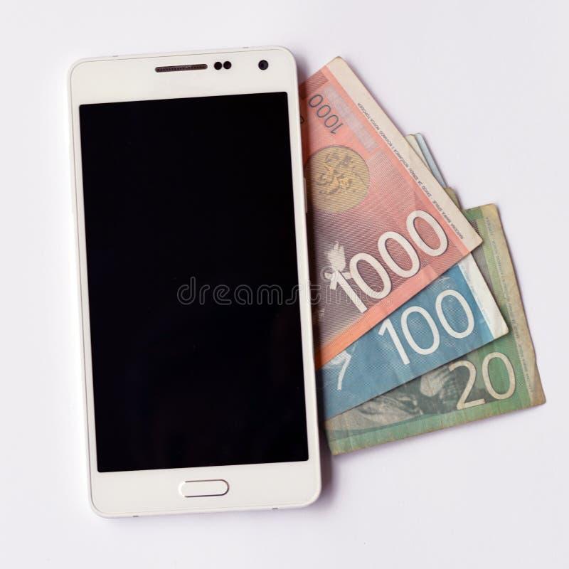 Telefono cellulare sopra le banconote serbe del dinaro fotografie stock
