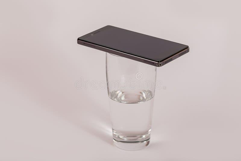 Telefono cellulare su un bicchiere d'acqua fotografie stock libere da diritti