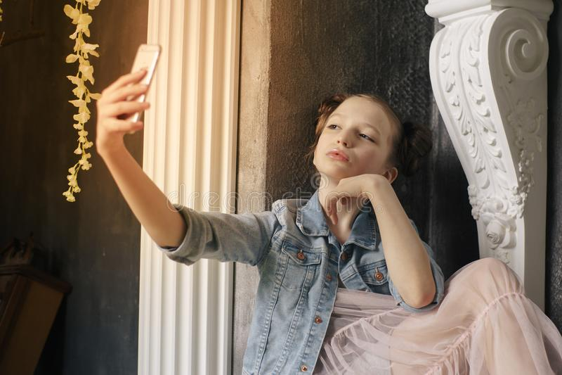Telefono cellulare teenager della tenuta della ragazza della scuola fotografia stock libera da diritti