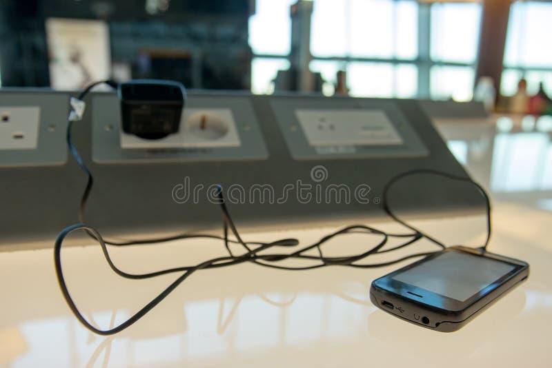 Telefono che fa pagare su una tavola fotografia stock libera da diritti