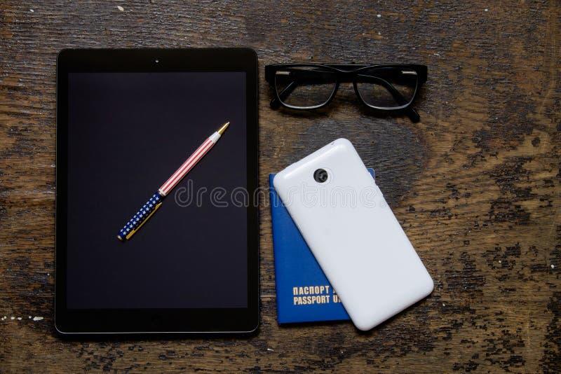 Telefono, compressa e blocco note sui vetri della tavola immagini stock