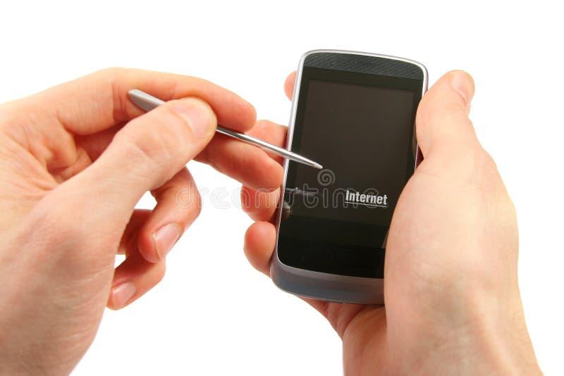 Telefono con lo schermo di tocco nelle mani fotografia stock