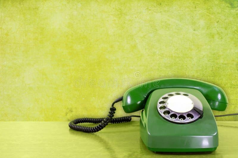 Telefono contro la parete verde fotografia stock