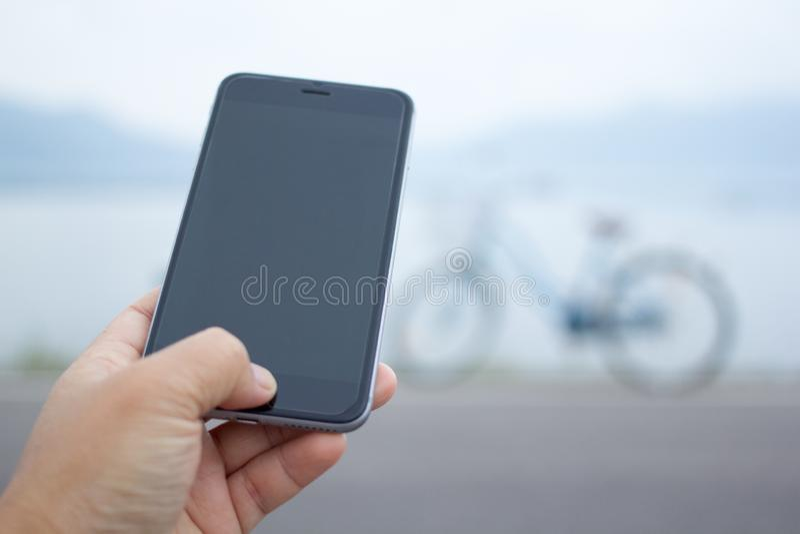 Telefono della tenuta della mano con la bicicletta della sfuocatura immagini stock libere da diritti