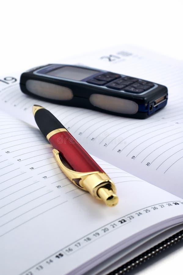 Telefono delle cellule e della penna nell'ordine del giorno aperto fotografie stock libere da diritti