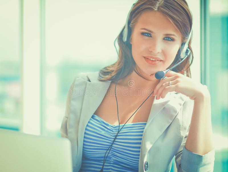 Telefono di conversazione della donna di affari mentre lavorando al suo computer all'ufficio fotografie stock