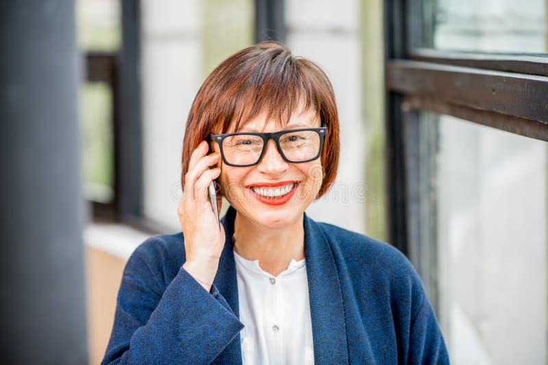 Telefono di conversazione della donna di affari più anziana all'interno fotografia stock libera da diritti